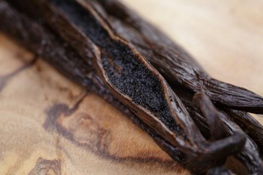 open vanilla pod on olive board, close up photo